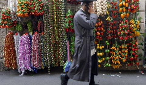epa01871789 An ultra-Orthodox Jewish man on his telephone passes decorations for the Sukkot holiday on display on a Jerusalem sreeet on 23 September 2009. Sukkot, or the week-long Feast of Tabernacles, commemorates the Israelites wandering the the desert for 40 years.  EPA/MIRIAM ALSTER ISRAEL OUT